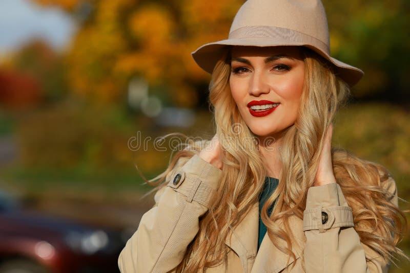 Piękna kobieta ono uśmiecha się w jesień kapeluszu żółty klonu ogródu tło Zakończenie portret fotografia stock