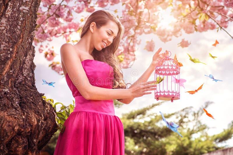 Piękna kobieta otaczająca mnóstwo motylami - chwyt wręcza birdcage - fotografia royalty free