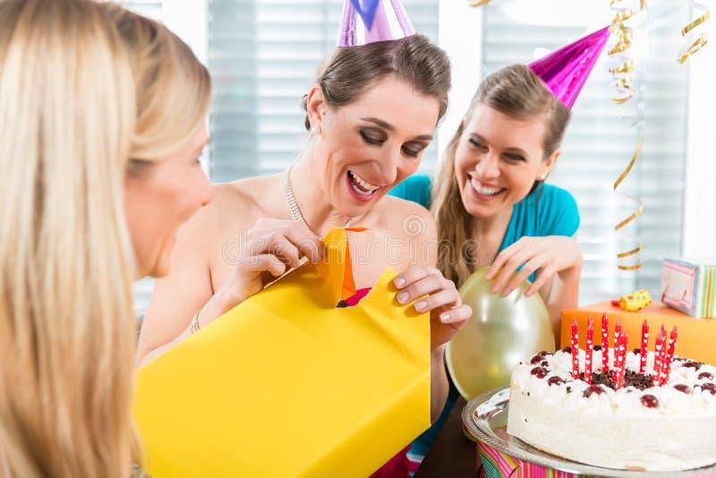 Piękna kobieta otwiera prezenta pudełko podczas gdy świętujący jej birthda obraz stock