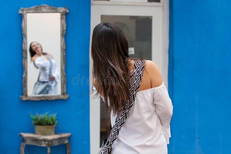 Piękna kobieta patrzeje ją na lustrze na kolorowych ulicach kolonista na biel sukni izolował miasto Cartagena de zdjęcie stock