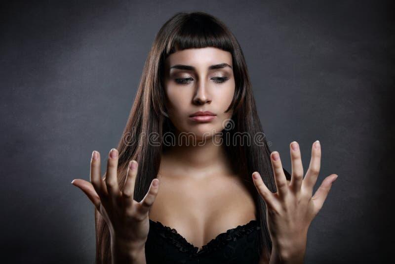 Piękna kobieta patrzeje jej ręki fotografia stock