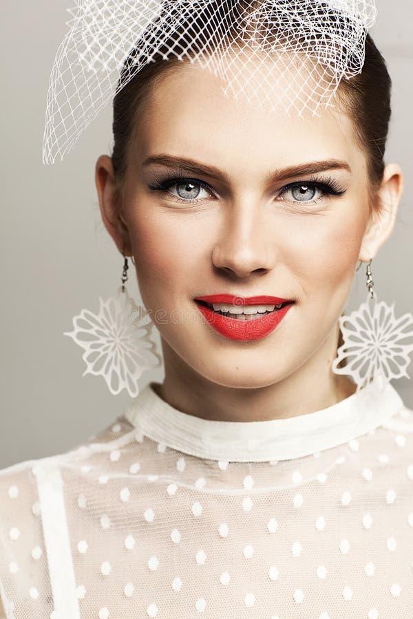Piękna kobieta patrzeje naprzód z eleganckim kapeluszem i elegancką białą kropkowaną bluzką obraz stock