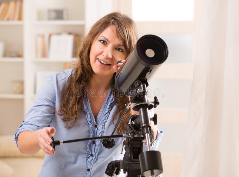 Piękna kobieta patrzeje przez teleskopu zdjęcia stock