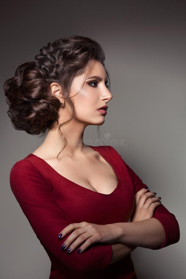 Piękna kobieta patrzeje w dół nad ramieniem z eleganckim ostrzyżeniem i dużymi kolczykami, wzruszająca szyja ręką brunetki dziewc zdjęcia stock