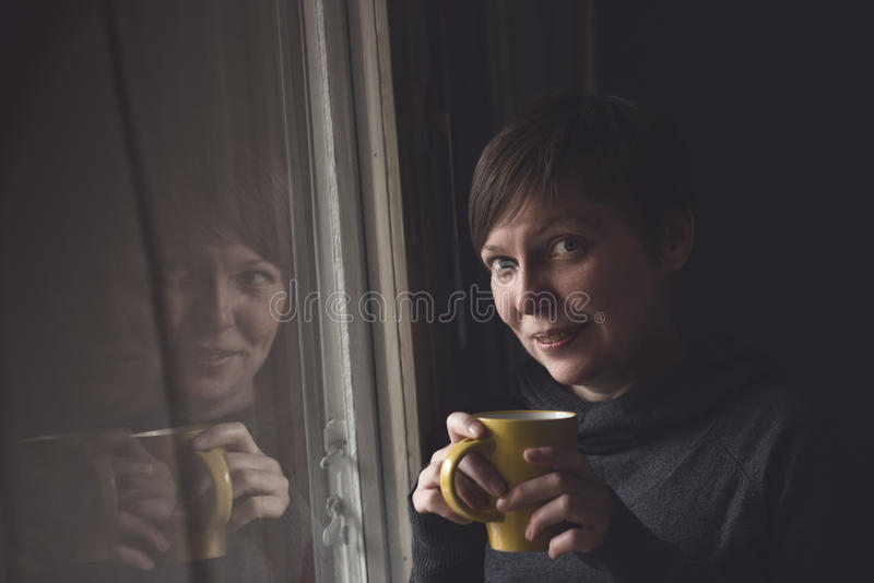 Piękna kobieta Pije kawę w Ciemnym pokoju fotografia royalty free