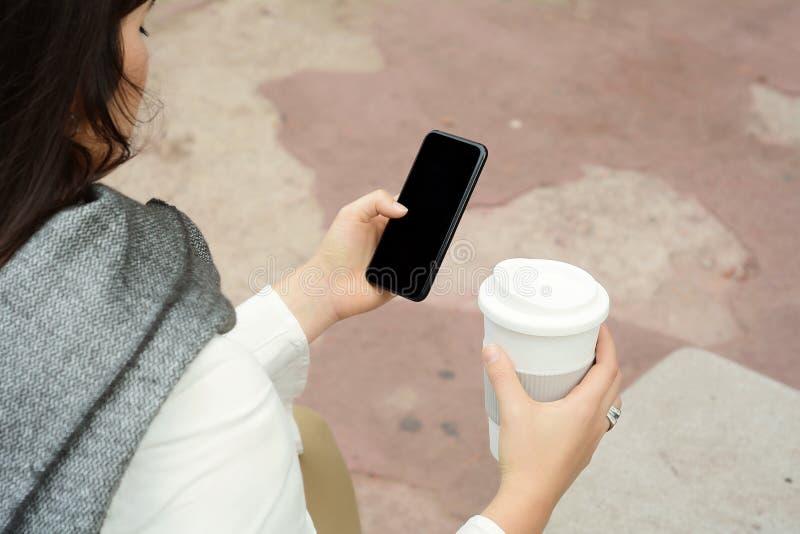 Piękna kobieta pije papierową filiżankę kawy i używa jej pho zdjęcie royalty free