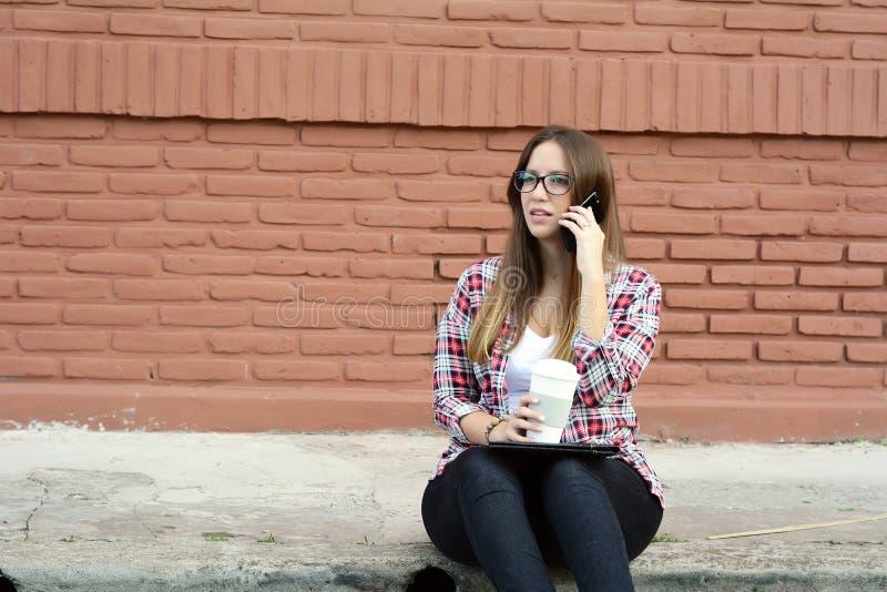 Piękna kobieta pije papierową filiżankę kawy i używa jej pho obraz stock