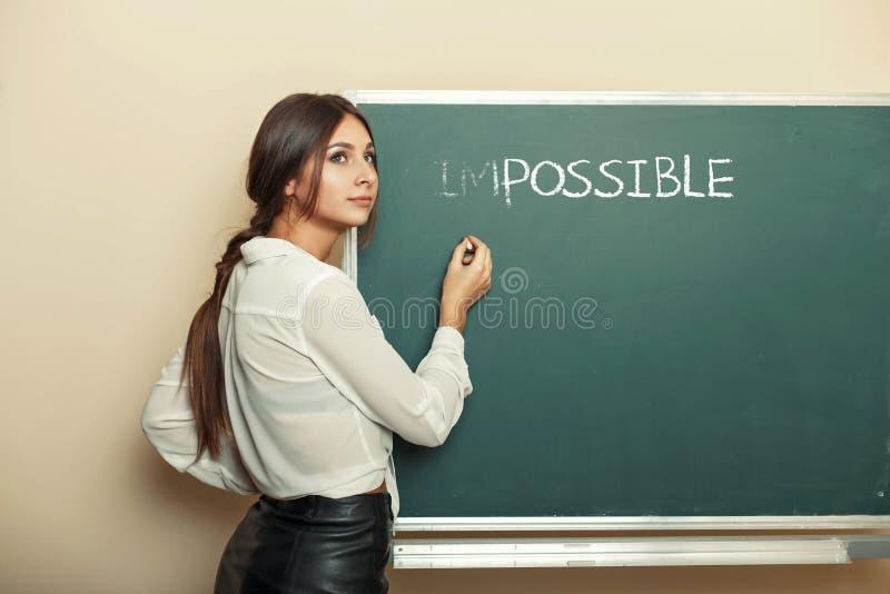 Piękna kobieta pisze na blackboard słowie niemożliwym obraz stock