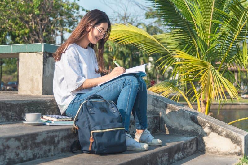 Piękna kobieta pisze w jej dzienniczek w parku, zdjęcia royalty free