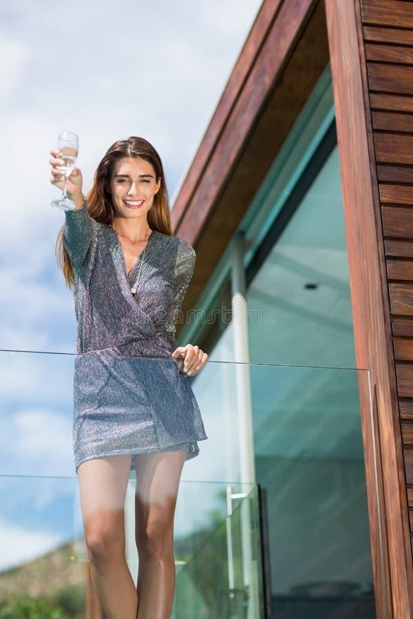 Piękna kobieta pokazuje szampańskiego flet przy balkonem zdjęcie royalty free