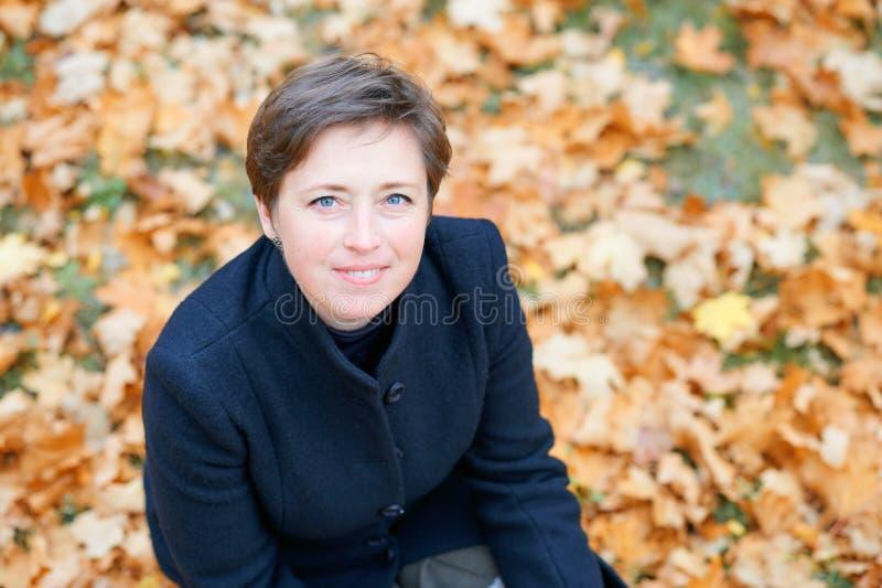Piękna kobieta pozująca się żółtych liści w jesiennym parku, sezon jesienny fotografia royalty free