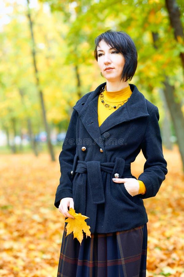 Piękna kobieta pozująca się żółtych liści w jesiennym parku, sezon jesienny fotografia stock