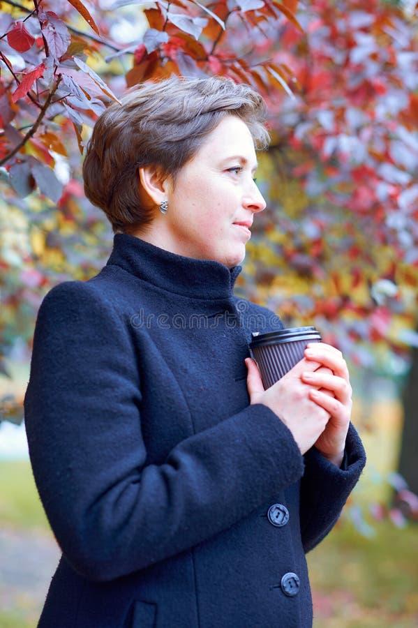 PiÄ™kna kobieta pozujÄ…ca z papierowym kubkiem herbaty lub kawy w jesiennym parku, sezon jesienny zdjęcie royalty free