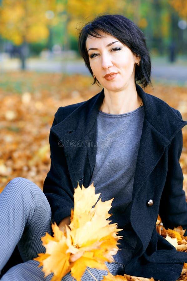 Piękna kobieta pozuje z żółtymi liśćmi w jesieni miasta parku, sezon jesienny zdjęcie stock
