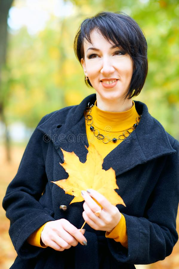 Piękna kobieta pozuje z żółtymi liśćmi w jesieni miasta parku, sezon jesienny fotografia stock