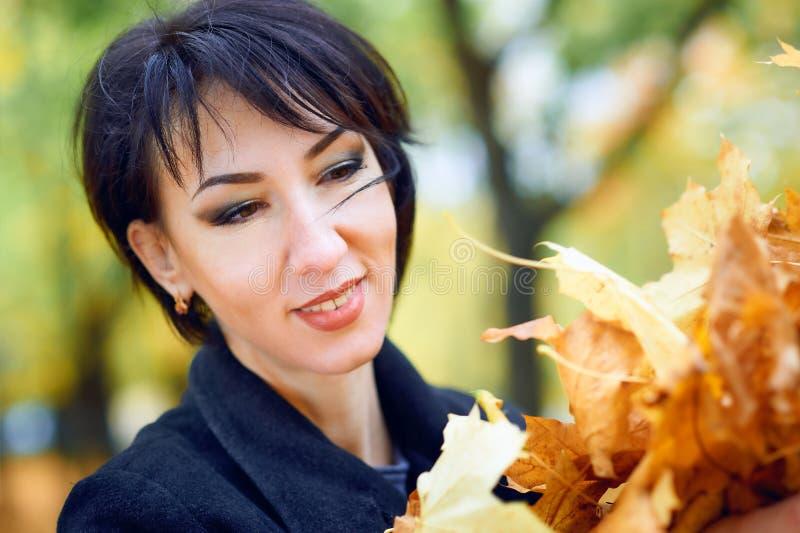 Piękna kobieta pozuje z żółtymi liśćmi w jesieni miasta parku, sezon jesienny fotografia royalty free