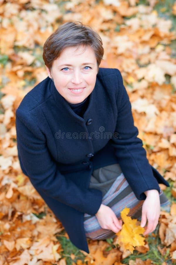 Piękna kobieta pozuje z żółtymi liśćmi w jesieni miasta parku, sezon jesienny obrazy royalty free