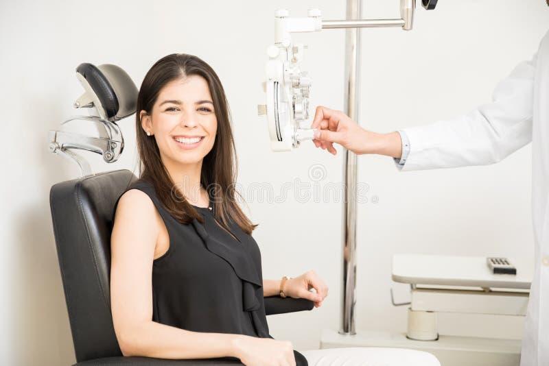 Piękna kobieta przechodzi oko test z phoropter w okulistycznym st obrazy stock