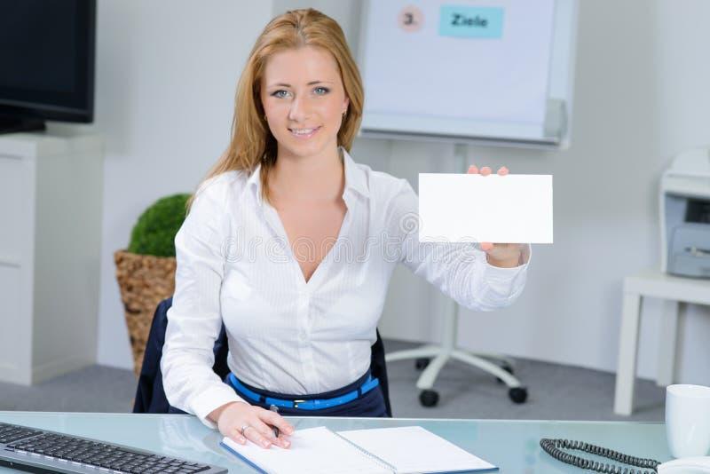 Piękna kobieta przy biurem pokazuje wizytówkę zdjęcia royalty free