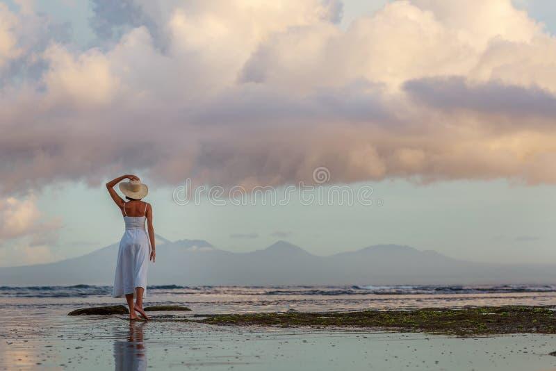 Piękna kobieta przy oceanie o zachodzie słońca obrazy royalty free