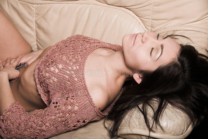 Piękna kobieta relaksuje na białej kanapie zdjęcie stock
