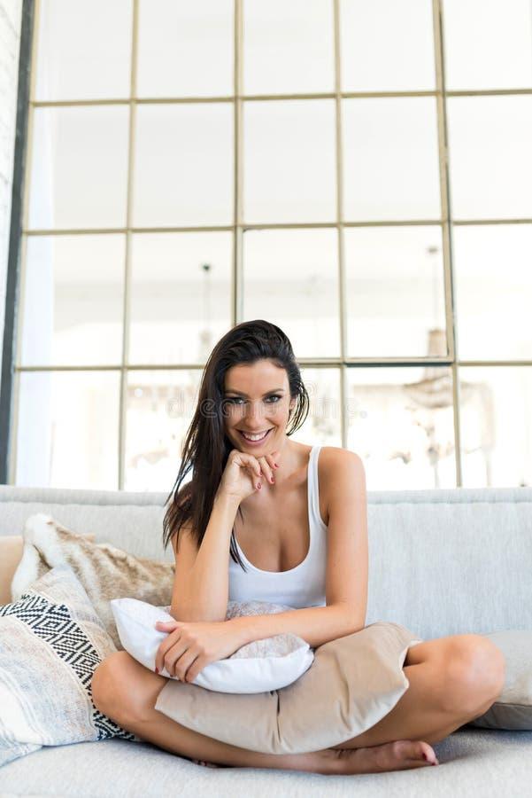 Piękna kobieta relaksuje w domu na kanapie obraz royalty free
