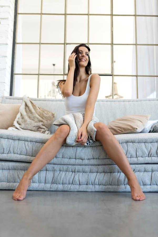 Piękna kobieta relaksuje w domu na kanapie fotografia royalty free