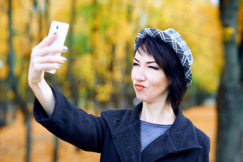 Piękna kobieta robiąca selfie smartfonem i bawiąca się w jesiennym parku, sezon jesienny, żółte liście obraz royalty free