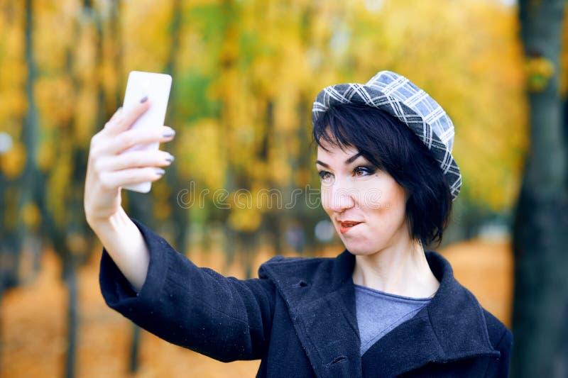 Piękna kobieta robiąca selfie smartfonem i bawiąca się w jesiennym parku, sezon jesienny, żółte liście obraz stock