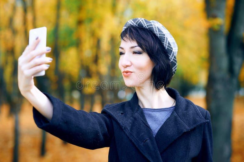 Piękna kobieta robiąca selfie smartfonem i bawiąca się w jesiennym parku, sezon jesienny, żółte liście obrazy stock
