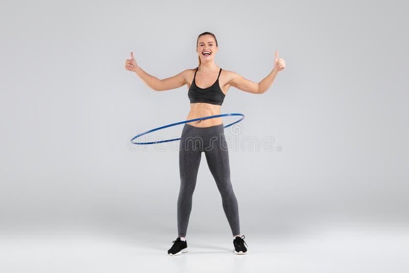 Piękna kobieta robi ćwiczeniom z hula obręczem obraz stock