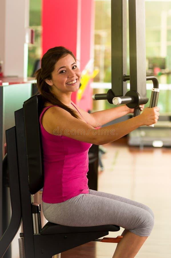 Piękna kobieta robi klatce piersiowej ćwiczy w gym zdjęcia royalty free