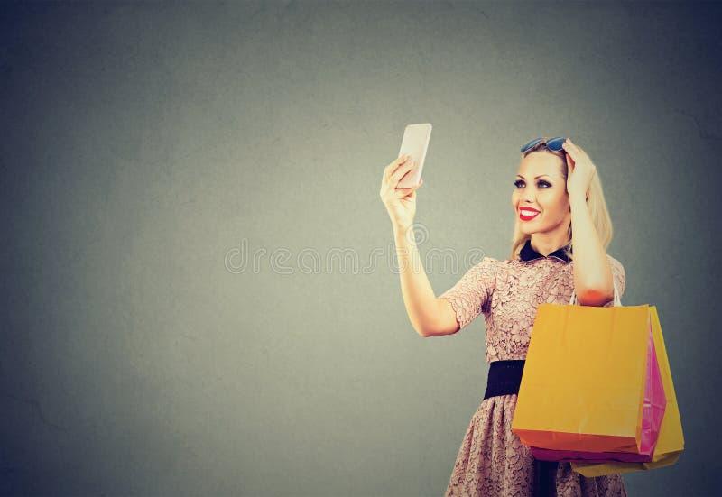 Piękna kobieta robi zakupy online brać selfies na telefonie komórkowym obrazy stock