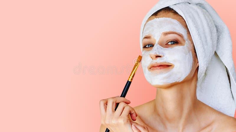 Piękna kobieta stosuje twarzową maskę na jej twarzy z muśnięciem Sk?ry traktowanie, opieka, zdr?j, naturalny pi?kno i kosmetologi obraz royalty free