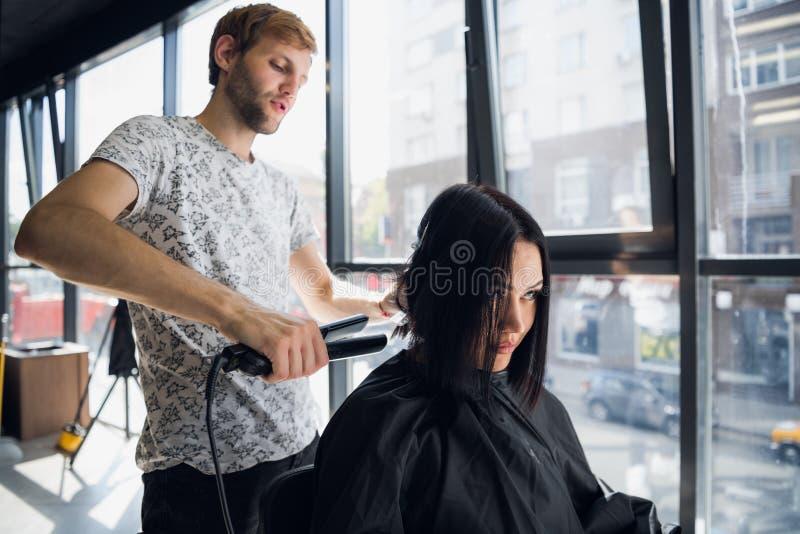 Piękna kobieta szczęśliwa podczas gdy fryzjer prostuje jej włosy w salonie Nowy ostrzyżenie lub fryzura dla młodej kobiety fotografia royalty free