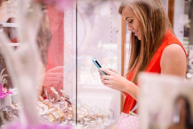 Piękna kobieta texting podczas gdy wybierający wristwatch zdjęcia royalty free