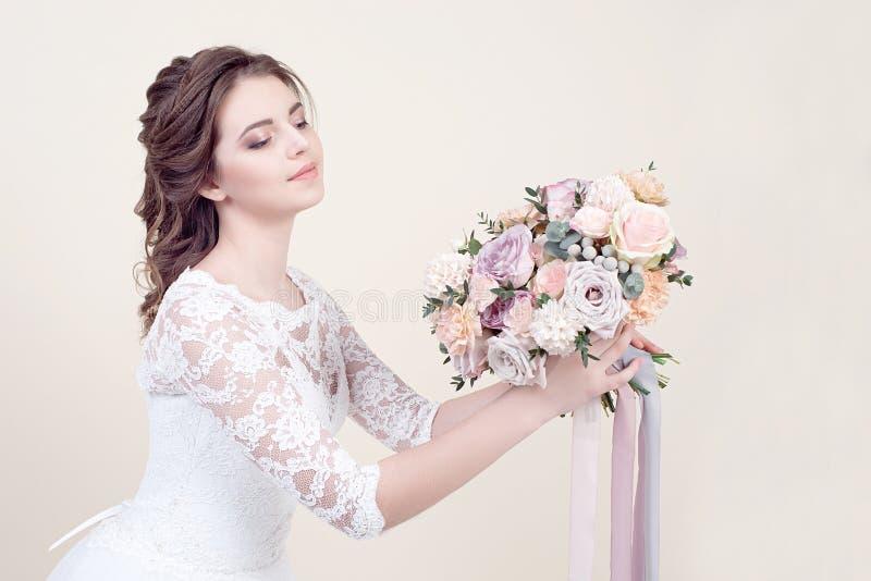 Piękna kobieta trzyma bukiet kwiaty jest ubranym w luksusowej ślubnej sukni odizolowywającej na tle obraz stock