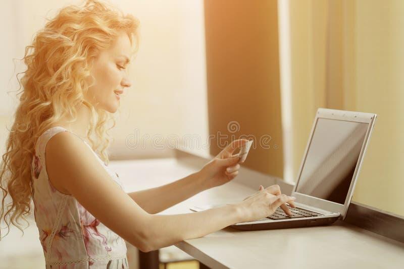Piękna kobieta trzyma kredytową kartę w ręce i wchodzić do ochrona kod używać laptop klawiaturę obrazy royalty free
