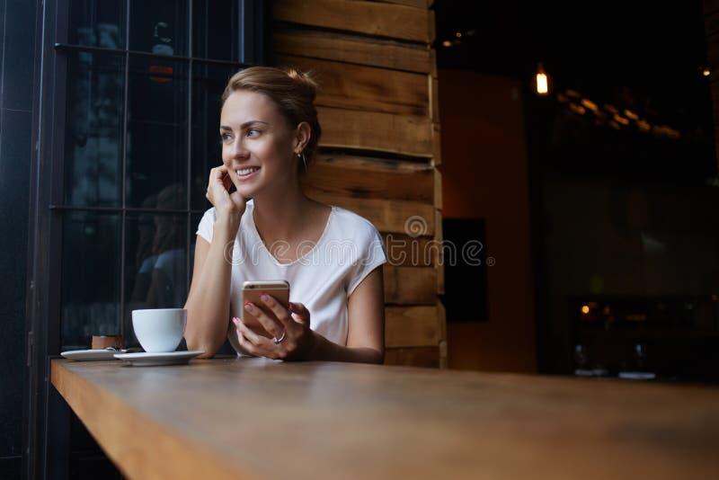 Piękna kobieta trzyma mądrze telefon z ślicznym uśmiechem podczas gdy siedzący w kawiarnia barze podczas jej rekreacyjnego czasu, obraz stock