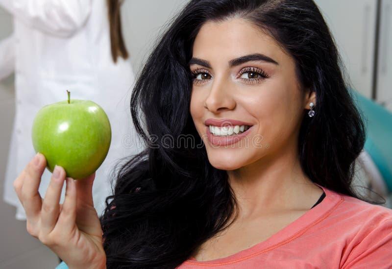 Piękna kobieta trzyma zielonego jabłka z doskonalić białymi zębami fotografia stock