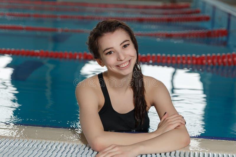 Piękna kobieta uśmiechnięta i patrzeje kamera przy granicą pływacki basen zdjęcia royalty free