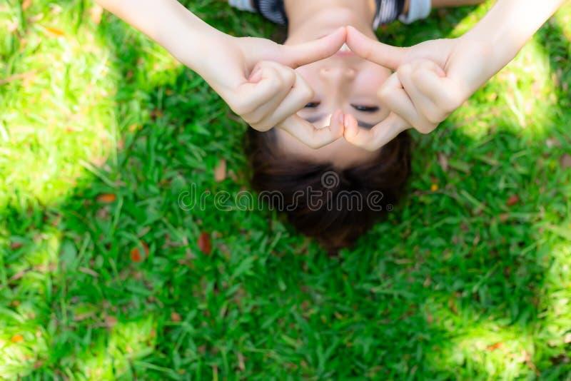 Piękna kobieta używa jej palce, ręki robić i symbolowi lub sercu miłość Powabna piękna kobieta jest łgarskim puszkiem dalej fotografia stock