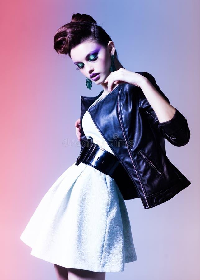 Piękna kobieta ubierał eleganckiego ruch punków pozuje w studiu zdjęcia stock