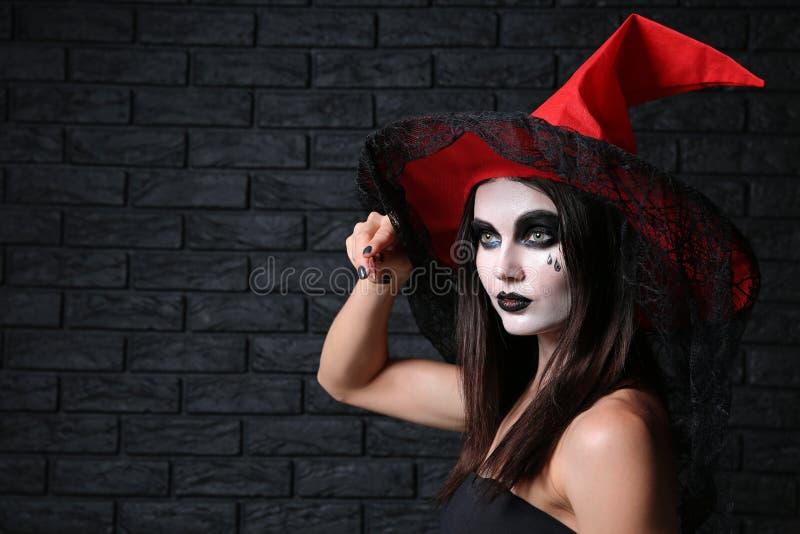 Piękna kobieta ubierał jako czarownica dla Halloween z magiczną różdżką na ciemnym tle zdjęcie royalty free