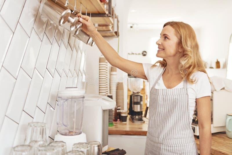 Piękna kobieta układa filiżanki w lokalnej kawiarni zdjęcie royalty free