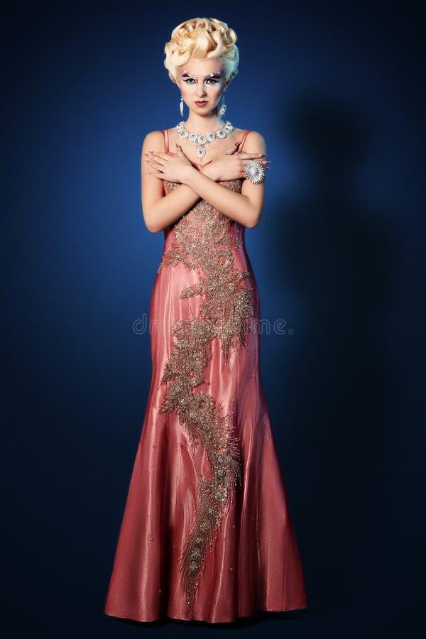 Piękna kobieta uzupełniał włosianego stylu luksusu menchii suknię obrazy royalty free