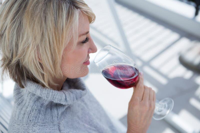 Piękna kobieta wącha czerwone wino w ganeczku fotografia stock