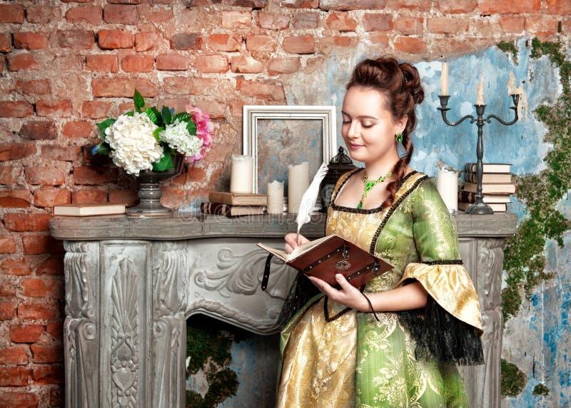 Piękna kobieta w średniowiecznym smokingowym writing w dzienniczku zdjęcia stock
