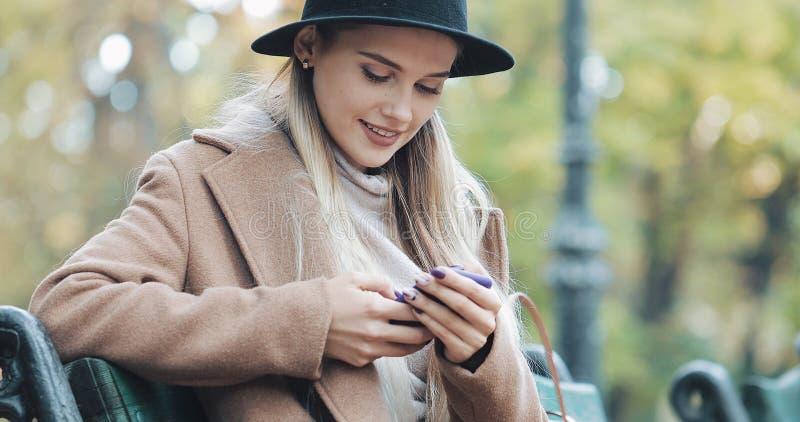Piękna kobieta w żakiecie używa smartphone relaksuje na ławce w jesień parku Technologia outdoors obraz royalty free