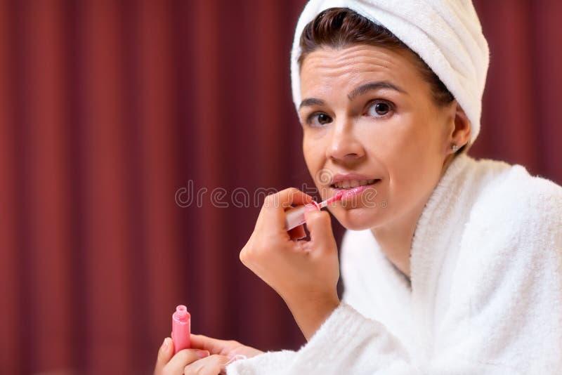 Piękna kobieta w bathrobe z ręcznikiem w jej kierowniczej stosuje pomadce zdjęcie royalty free